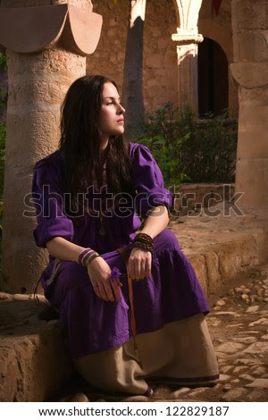 Brunette girl in a medieval suit in a Agia Napa Medieval Monastery background - stock photo
