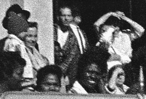 The Oswald Innocence Campaign says this photograph shows Lee Harvey Oswald (in the middle of the image, looking toward the camera) in the doorway of the book depository when JFK was shot