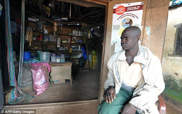 Um homem se senta na frente de um cartaz preventiva para o vírus Ebola hoje na entrada de uma loja em Dialadian, Senegal