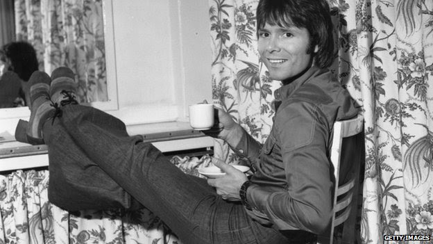 Pop star Cliff Richard relaxes with a cup of tea backstage, before the Royal Variety Performance at the London Palladium, 26 November 1973