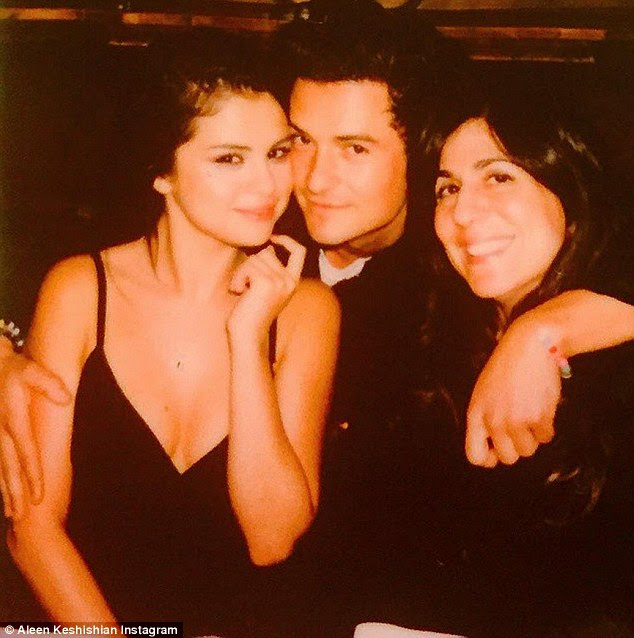Good times with an old pal: Selena Gomez cuddled up to Orlando Bloom at his 39th birthday bash; also in the frame is her manager Aleen Keshishian