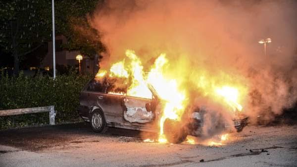 Vista de un vehículo en llamas tras los disturbios registrados en el barrio de Kista, en Estocolmo, Suecia. (Fredrik Sandberg / Efe)