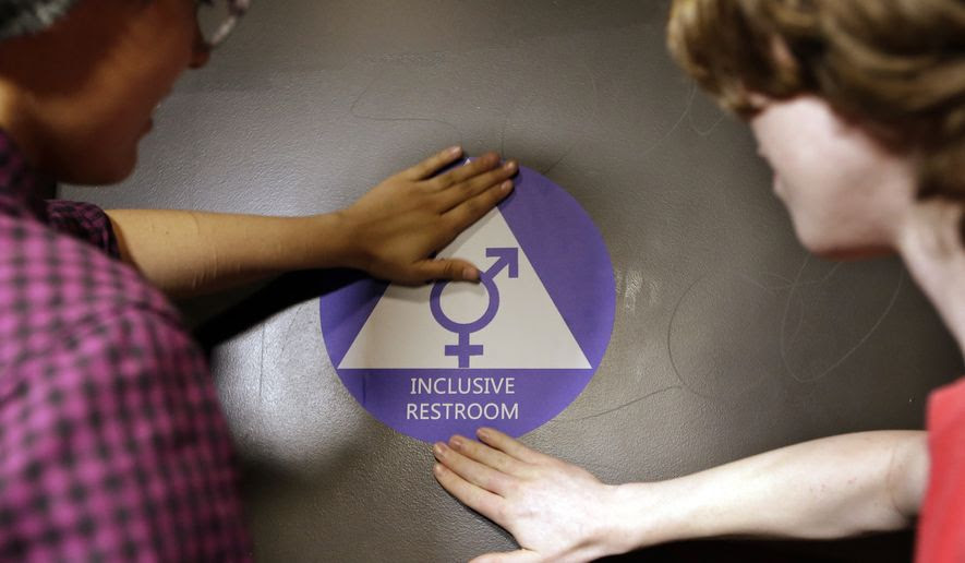 Destin Cramer, left, and Noah Rice place a new sticker on the door at the ceremonial opening of a gender neutral bathroom at Nathan Hale high school May 17 in Seattle. (Associated Press)