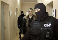 A TV grab from Russia's Channel One shows a man identified as Adam Osmayev (centre) -- one of the suspected militants conspiring to kill Vladimir Putin -- being escorted by the Ukrainian Security Service (SBU) shortly after his arrest in Odessa. (AFP Photo/)