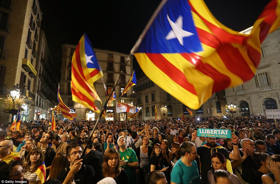 "In a televised address earlier today, Mr Puigdemont called plans by Mr Rajoy to replace him and his cabinet an ""attempt to humiliate"" Catalonia and an ""attack on democracy"". Pictured: Protesters watching the address"