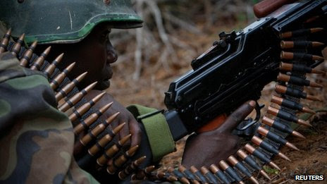 A soldier serving with the African Union Mission in Somalia (Amisom) takes cover in a firefight during a joint Amisom and Somali National Army operation to seize and liberate territories from Al-Shabaab militants in Daynile 22 May 2012