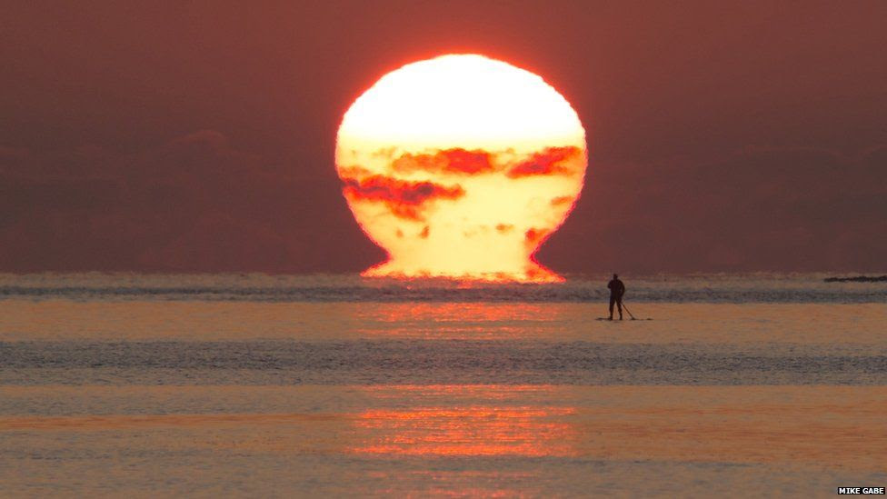 A man on a paddleboard in the sea as the sun sets