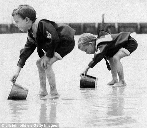 Children collect water while building a sandcastle