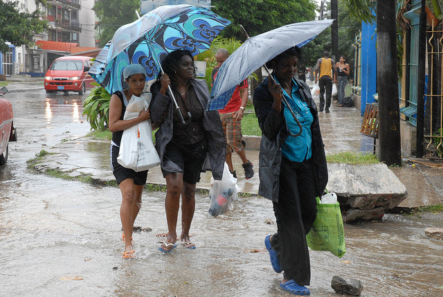 Several women walk in the rain towards their homes carrying food, as part of their preparations for the imminent arrival in Cuba of Hurricane Gustav, in 2008, in a Havana neighbourhood. Credit: Jorge Luis Baños/IPS
