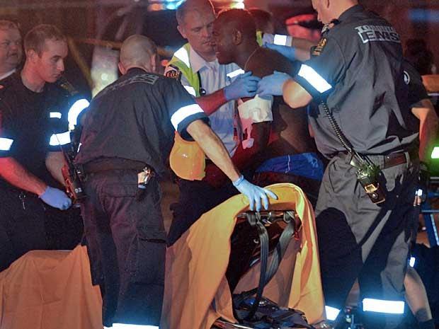 Um ferido recebe atendimento no local onde tiroteio mataram ao menos duas pessoas em Toronto, no Canadá. (Foto: Rick Madonik / The Canadian Press / Toronto Star / AP Photo)
