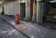A woman leaves a building that suffered some damage after an earthquake was felt in Mexico City, Tuesday March 20, 2012. A strong, long earthquake with epicenter in Guerrero state shook central southern Mexico, swaying buildings in Mexico City and sending frightened workers and residents into the streets. (AP Photo/Dario Lopez-Mills