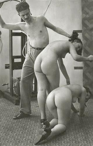Shirtless man whipping two nude women crawling