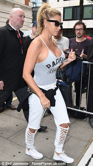 Bustin out: Katie, who underwent her eighth boob job earlier this year, added to her ensemble with a pair of distressed skinny jeans, while white trainers rounded things off