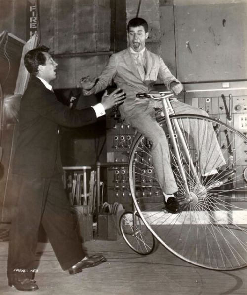 Jerry Lewis rides a high wheel. Dean Martin lends a hand.