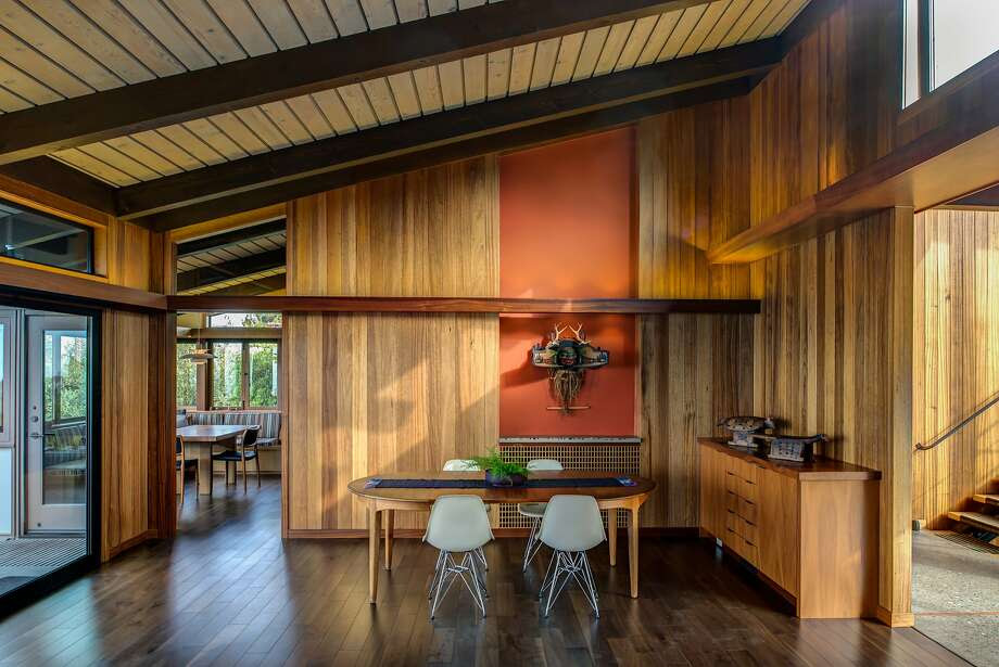 The dining room of the renovated midcentury home in the Berkeley hills displays a Tlingit sculpture on an accent wall painted in Benjamin Moore's Fiery Opal. (The same color appears on the front door.) Photo: Treve Johnson Photography