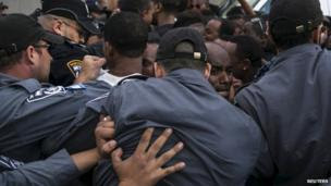 An Israeli of Ethiopian descent reacts as he is pushed by police officers during a protest in Tel Aviv, Israel, on 3 May