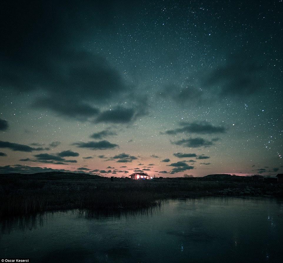 Endles céus: Uma única casa iluminada sob um céu estrelado parece atraente neste tiro ao lago em Jurmo, Finlândia