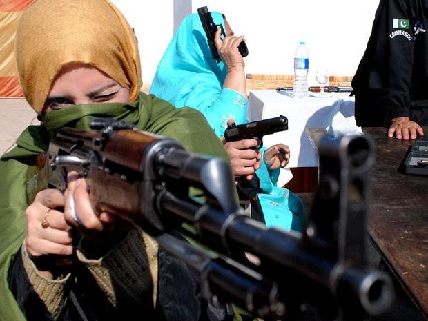 Professora maneja arma durante treinamento de segurança no Paquistão (Foto: Mohammad Sajjad/AP)