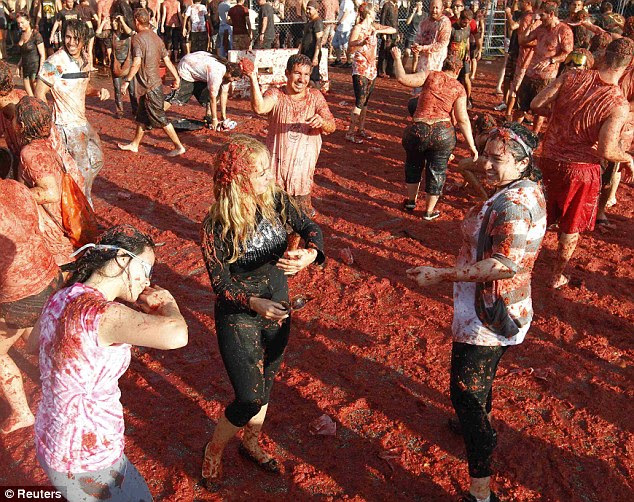 Action: Residents of Miami recreated Spain's La Tomatina Tomato Fight Festival Saturday afternoon tossing 25,000 tomatoes at one another in a bar's parking lot