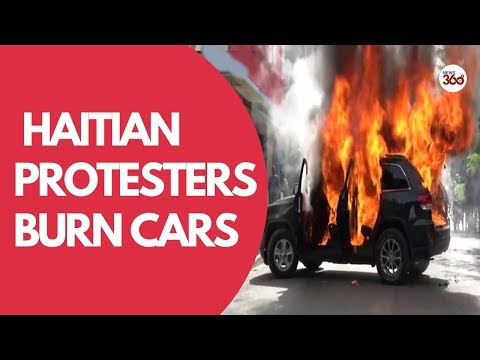 Haiti : Protesters torch cars & demand release of detained officer in Po...