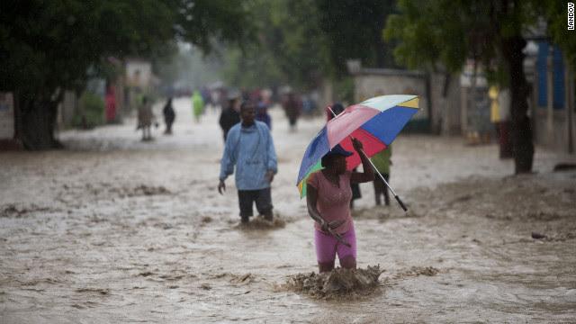 People walk on a flooded street after Hurricane Sandy hit Port-au-Prince, Haiti, on Thursday.