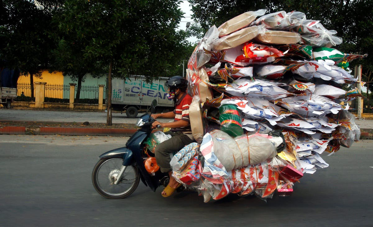 A man transports paper replicas of many items to be sold for the Vu Lan Festival in Vietnam. During the festival, Taoists and Buddhists believe that the living are supposed to please ghosts by offering food and burning paper effigies of daily items.