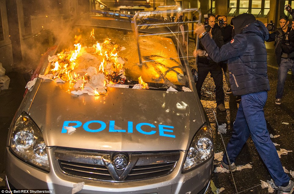 The protestor clad in his expensive  jacket, similar versions of which retail for between £100 and £500, could be seen attacking the police car's windscreen with a metal frame