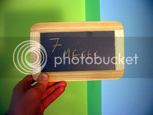 Quadro em lousa, segurado pela mão em frente a uma parede verde e azul, onde se pode ler: 7 meses
