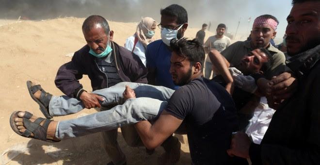 Varias personas trasladan un hombre herido durante las protestas del lunes en Gaza. - REUTERS