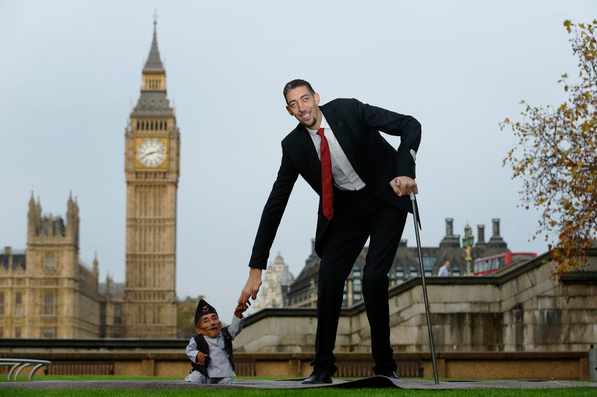 The world's shortest man, Chandra Bahadur Dangi, greets the tallest living man, Sultan Kosen, to mark the Guinness World Records Day in London Nov. 13, 2014.  Kosen, measuring more than 8 feet tall, towers over Dangi who is only 1.8 feet tall. The Guinness World Records celebrates its 60th edition of the annual records book this year.