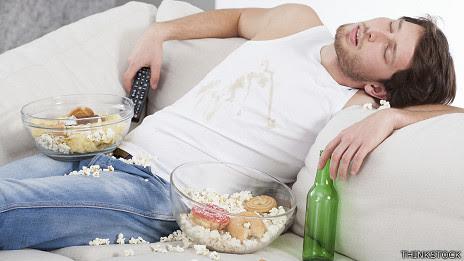 Hombre dormido en el sofa con comida