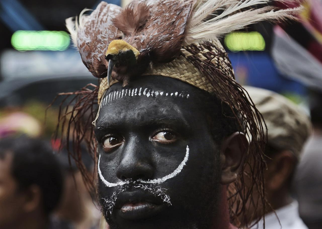 In this Monday, March 20, 2017 photo, a Papuan activist donning a traditional headwear with a stuffed bird of paradise attends a protest against U.S. mining giant Freeport-McMoRan Copper & Gold Inc. in Jakarta, Indonesia. A group of activists staged the protest demanding the New Orleans-based mining company close its mine in Papua province saying that it siphons off the region's wealth and gives it little in return.