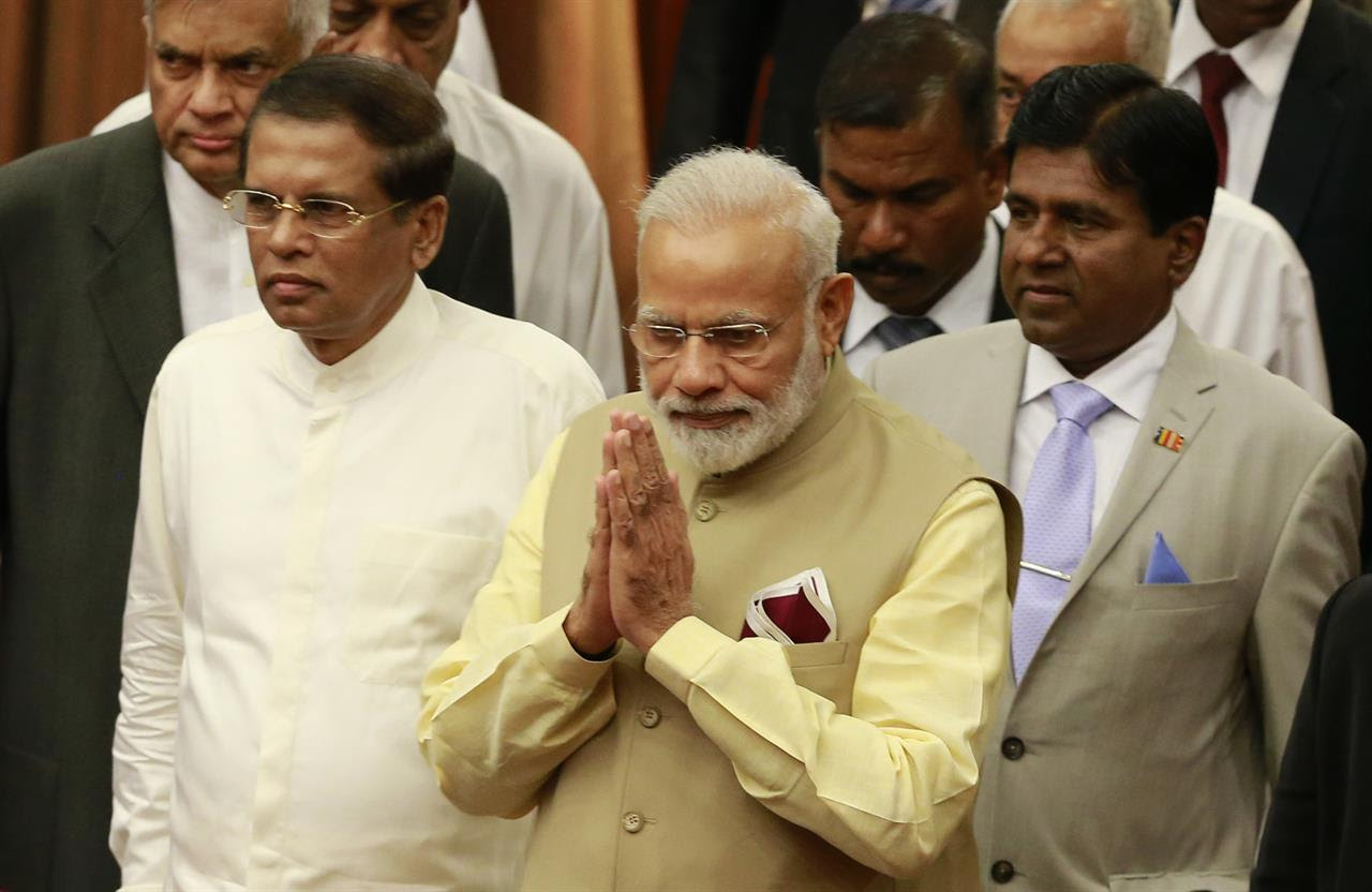 Indian Prime Minister Narendra Modi, center, greets the delegates as he arrives at UN celebration ceremony of Vesak or Buddha Purnima with Sri Lankan President Maithripala Sirisena, second left, and Sri Lankan Prime Minister Ranil Wickremesinghe, left, in Colombo, Sri Lanka, Friday, May 12, 2017. During his two-day visit Modi participated in the United Nations celebration of Vesak or the day of birth, enlightenment and death of the Buddha. He also inaugurated a modern hospital for the benefit of tea plantation workers , ancestors of Indian laborers brought by the British from the 18th century.