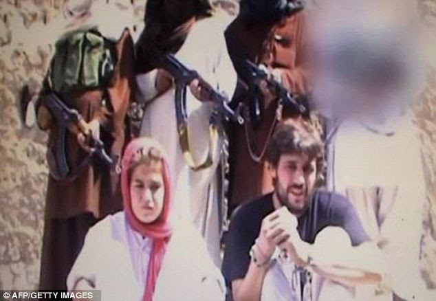 In danger: This video grab released in October shows the couple in front of Taliban gunman after they were abducted