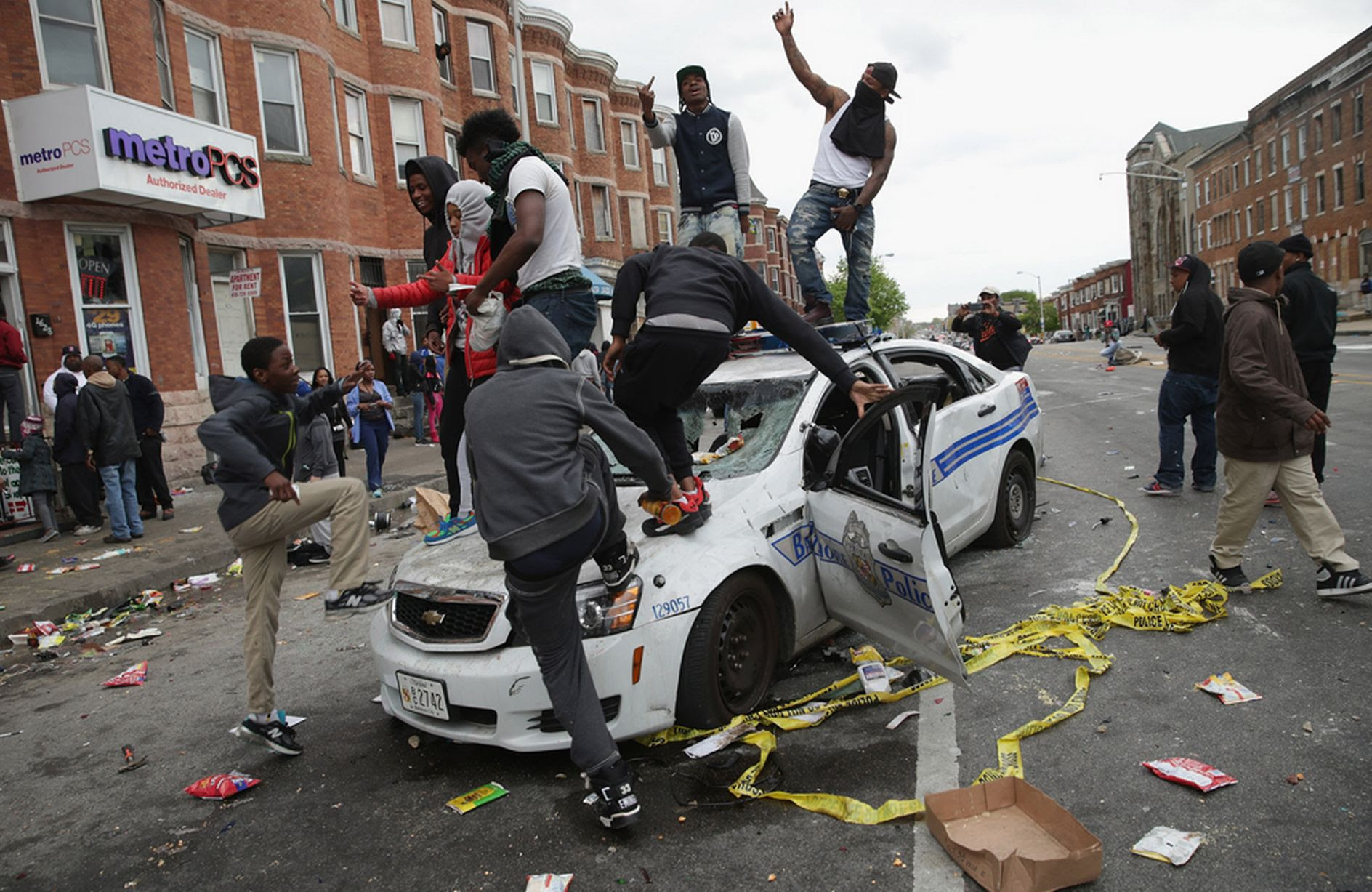 Demonstrators climb on a destroyed Baltimore Police car