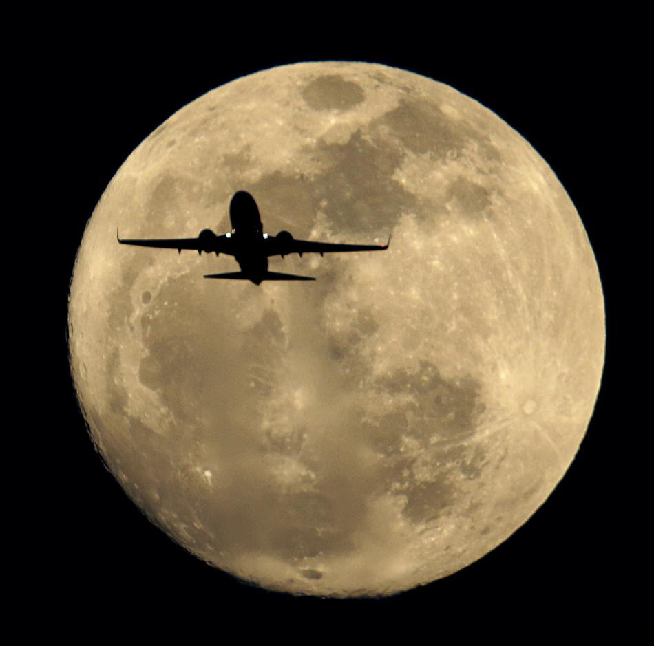 Αεροπλάνο πλησιάζει το αεροδρόμιο του Χήθροου για προσγείωση, με φόντο το «Φεγγάρι του Θερισμού» (η πανσέληνος που είναι κοντά στη φθινοπωρινή ισημερία ονομάζεται κατά την «Φεγγάρι του Θερισμού» , και δηλώνει την περίοδο όπου οι αγρότες ξεκινούν τη συγκομιδή των καλλιεργειών.)