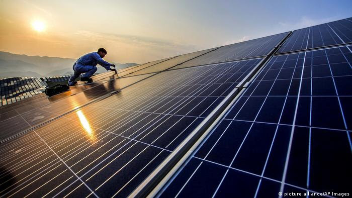 worker performs maintenance on solar panels at a photovoltaic power station in Songxi county in southeastern China's Fujian province (picture alliance/AP Images)
