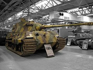 A large, turreted tank with dull yellow, green and brown wavy camouflage, on display inside a museum. The tracks are wide, and the frontal armor is sloped. The long gun overhangs the bow by several meters.