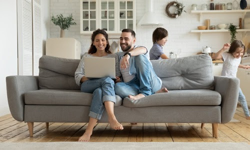kids running parents resting on sofa using laptop