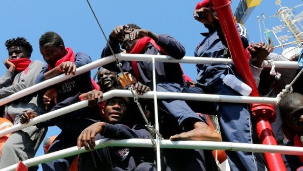 Migrants wait to disembark from the Vos Hestia ship as they arrive in the Crotone harbor, Italy, after being rescued off the Libyan coast.