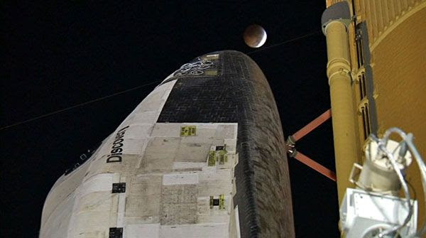 A total lunar eclipse is about to take place above space shuttle Discovery on the night of December 20, 2010.