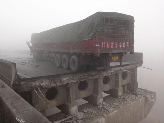 Um dos caminhões que trafegava no local da explosão ficou a poucos centimetros de cair após ponte desabar (Foto: Reuters)
