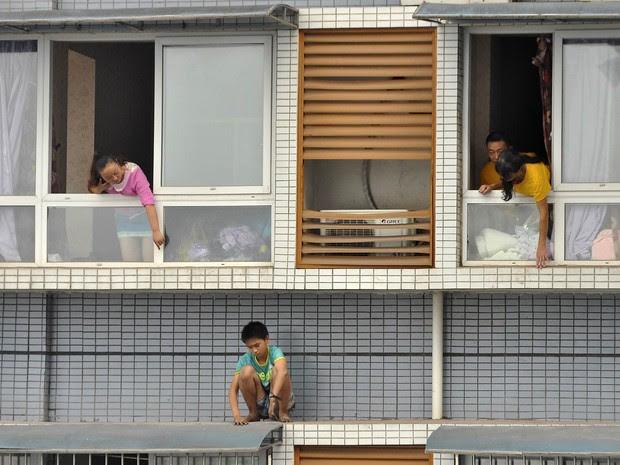 Familiares tentam convencer um menino de 12 anos a voltar para dentro do apartamento no 11º andar em Yibin, China. Ele estava com medo de ser punido por não terminar o dever de casa. Após 2 horas, ele voltou, convencido pela família e pela polícia (Foto: Reuters/Stringer)