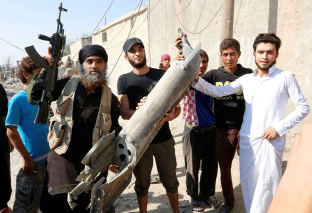 An Islamic State militant (L) stands next to residents as they hold pieces of wreckage from a Syrian war plane after it crashed in Raqqa, in Syria September 16, 2014.