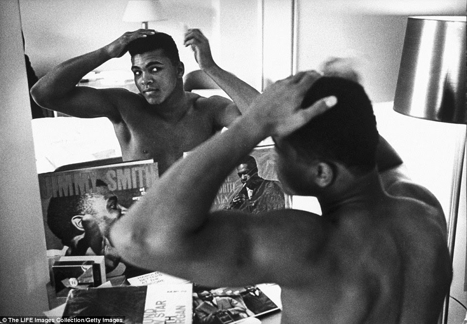 Then Cassius Clay, Ali combs his hair in the mirror before taking a walk in Pittsburgh on the day of his fight with Powell in January 1963