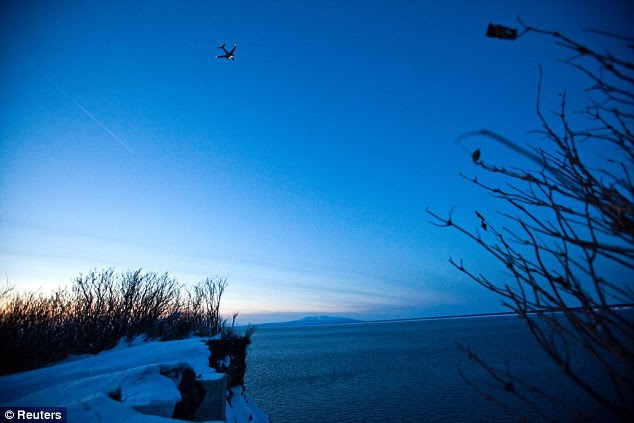 Calm before the storm: A passenger plane approaches Ted Stevens Anchorage International Airport on Tuesday, a cold and clear day in Anchorage