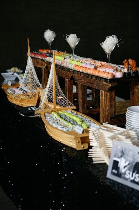 A sushi station displaying confections in wooden ships