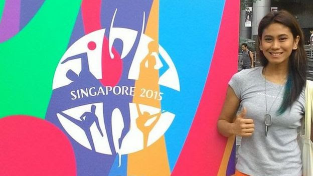 Alma Cabasal poses next to a billboard in Singapore
