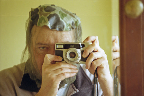 reflected self-portrait with Konica Z-UP 150 camera and camouflage net by pho-Tony