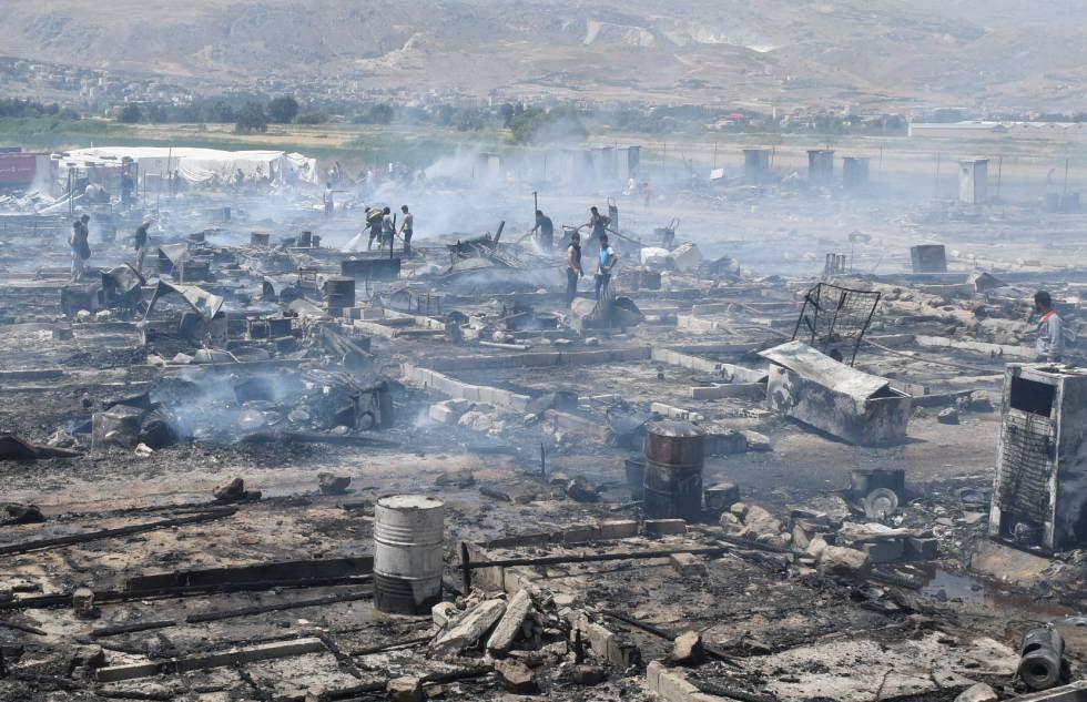 Miembros de Protección Civil y civiles apagan los rescoldos del fuego que ha arrasado un campo de refugiados del valle de la Bekaa.